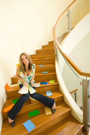 Young woman sitting on staircase and choosing color swatches : Stock Photo