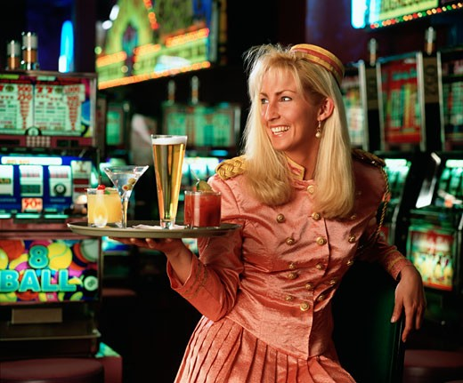 Stock Photo: 1574R-37460 Casino waitress holding a tray of drinks and smiling