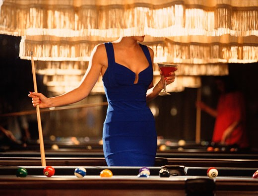 Woman in blue dress playing pool in a bar : Stock Photo