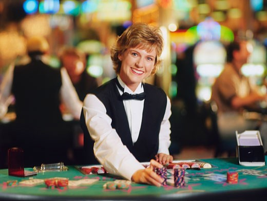 Female casino worker placing gambling chips on a table : Stock Photo
