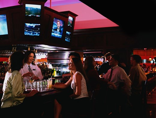 Group of people enjoying drinks in a bar : Stock Photo