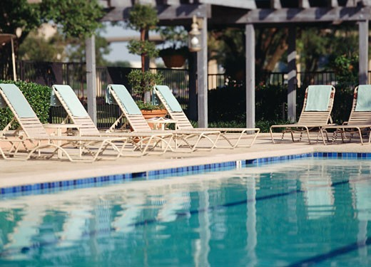 Lounge chairs at the poolside : Stock Photo