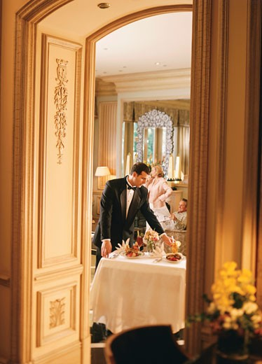 Stock Photo: 1574R-37472 Waiter serving food in a hotel room