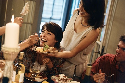 Woman eating from a plate held in front of her face at a dinner party : Stock Photo