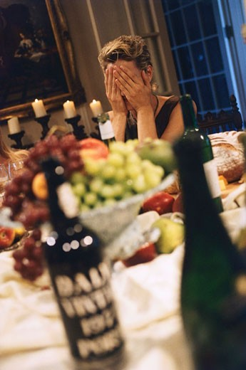 Woman covering her face at a dining table in a dinner party : Stock Photo