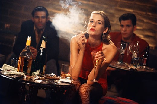 Stock Photo: 1574R-37476 Young woman smoking a cigar in a bar