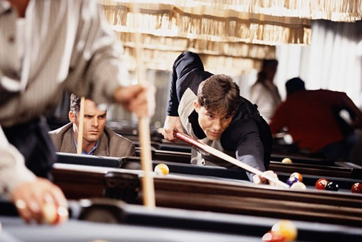 Men playing pool in a billiards bar : Stock Photo