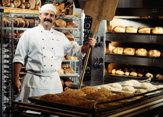 Portrait of a baker standing in a kitchen with breads : Stock Photo