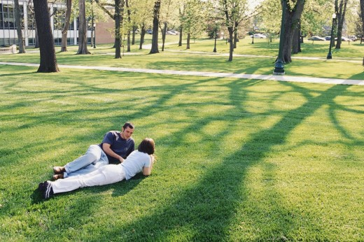 Young couple lying on the grass in the university campus : Stock Photo