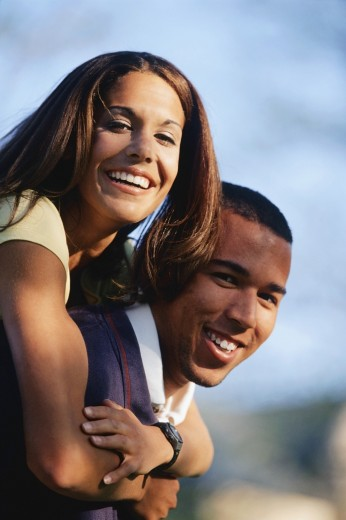 Young woman riding piggyback on her boyfriend : Stock Photo