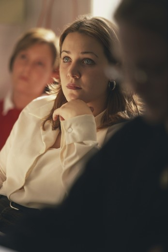 Young woman listening to a lecture in a university classroom : Stock Photo
