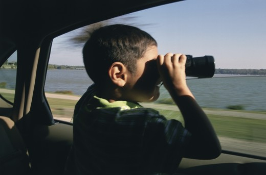 Boy sitting in a car and looking through binoculars : Stock Photo