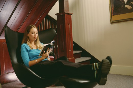 Young woman sitting on a chair and reading a book : Stock Photo
