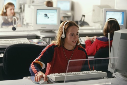 University students working in a computer lab and listening to headphones : Stock Photo