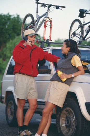 Stock Photo: 1574R-37497 Man talking on a mobile phone beside a woman leaning on a jeep with bikes mounted to the top