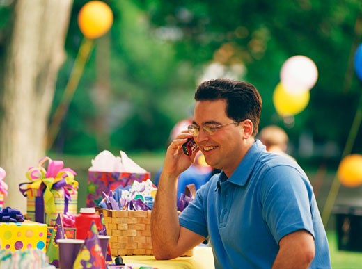 Mid adult man talking on a mobile phone in a birthday party : Stock Photo
