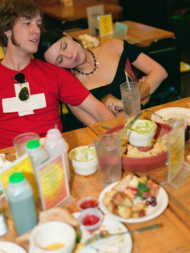 Young couple resting after eating at a restaurant : Stock Photo