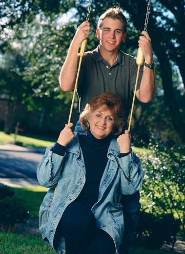 Young man with his mother on a swing : Stock Photo
