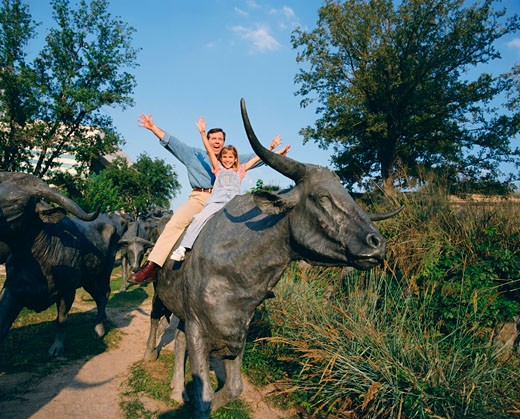 Man with his daughter sitting on a cow's sculpture : Stock Photo