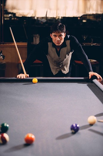 Man playing pool in a billiards bar : Stock Photo