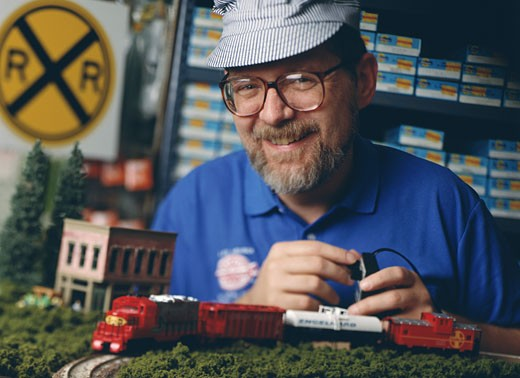Mature man operating a toy train : Stock Photo