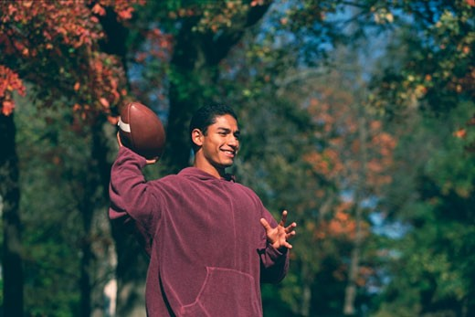Stock Photo: 1574R-37513 Young man throwing a football in a park