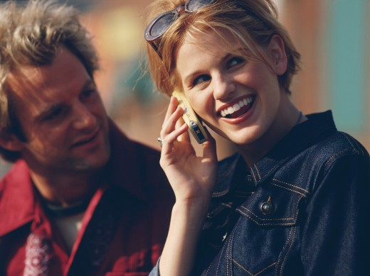 Mid adult woman talking on a mobile phone with a man looking at her : Stock Photo