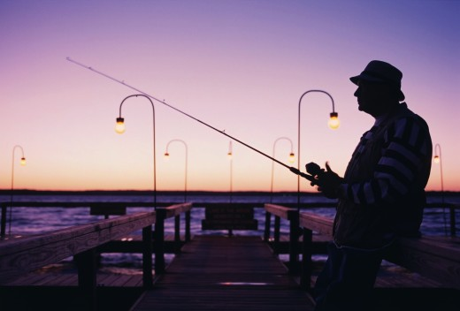 Mature man fishing on a dock in the morning : Stock Photo