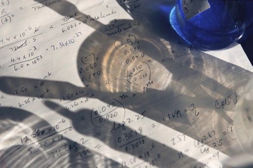 Stock Photo: 1574R-37529 Shadow of laboratory beaker and tools on science papers