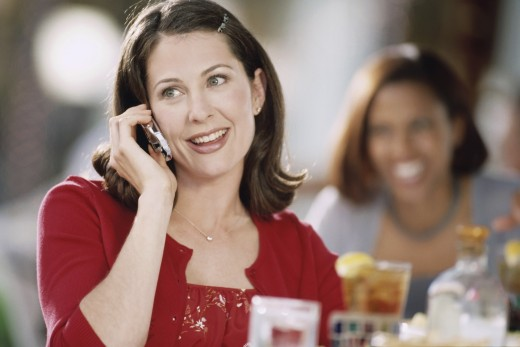 Mid adult woman talking on a mobile in a restaurant : Stock Photo