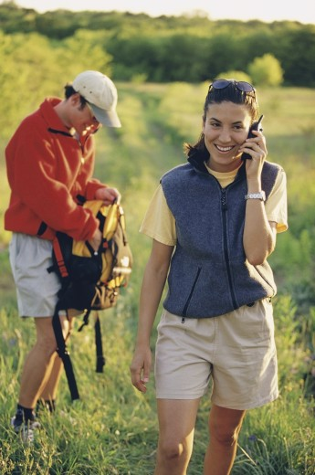 Mid adult woman talking on a mobile phone while hiking : Stock Photo