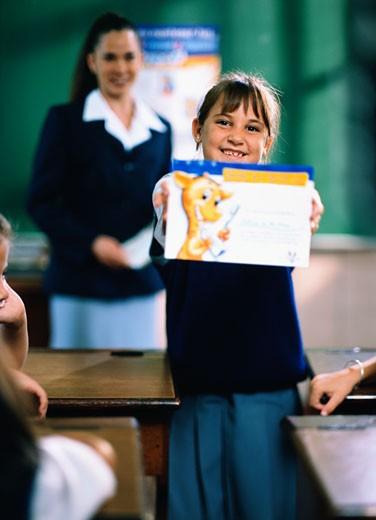 Stock Photo: 1574R-37538 Schoolgirl showing her award