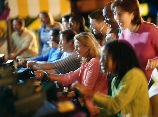 Stock Photo: 1574R-37541 People playing video games in an amusement arcade