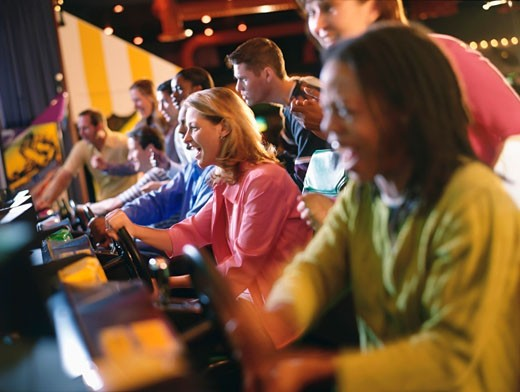 Stock Photo: 1574R-37543 People playing video games in an amusement arcade