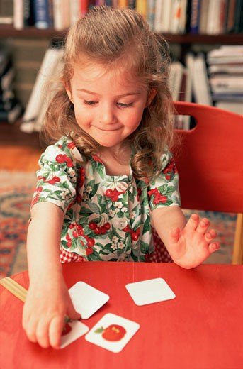 Girl playing cards game on a table : Stock Photo