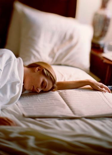 Stock Photo: 1574R-37548 Young woman sleeping on the bed near a newspaper