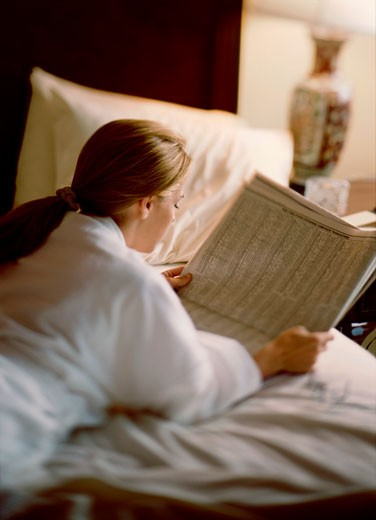 Young woman reading a newspaper on the bed : Stock Photo