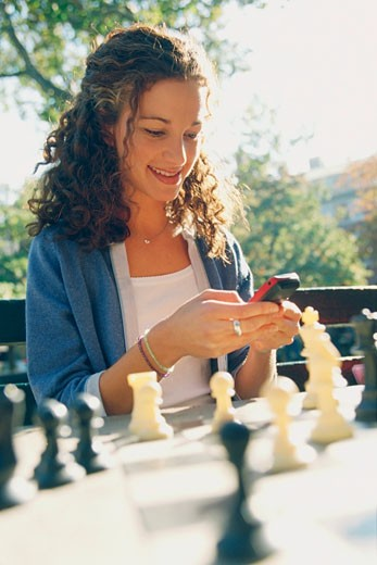 Young woman text messaging on mobile phone while playing chess : Stock Photo