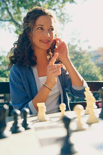 Young woman talking on the phone while playing chess : Stock Photo
