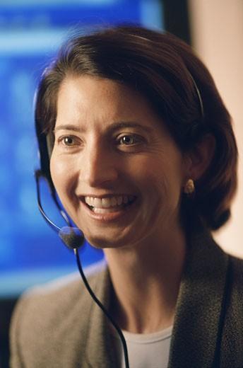 Close-up of a female customer service representative smiling : Stock Photo