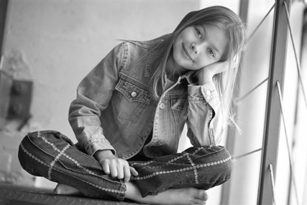 Young girl sitting cross legged : Stock Photo