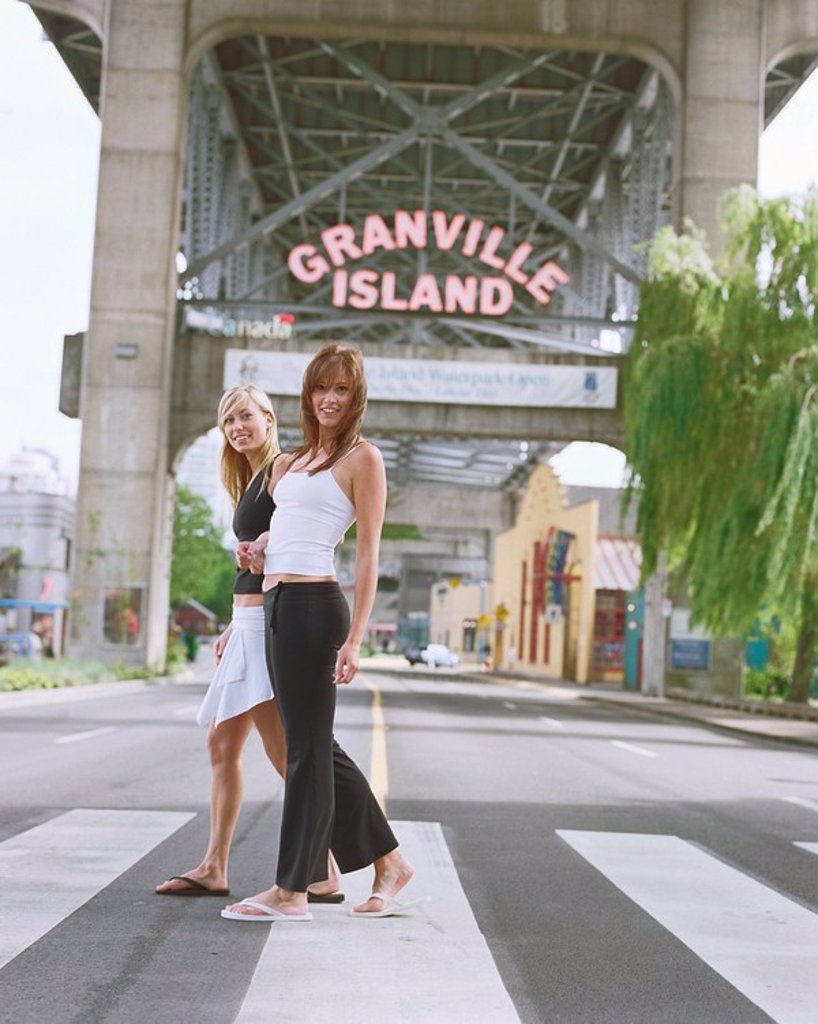 Stock Photo: 1575-5683 Two women walking across a cross_walk with Granville Island sign behind them _ Vancouver BC
