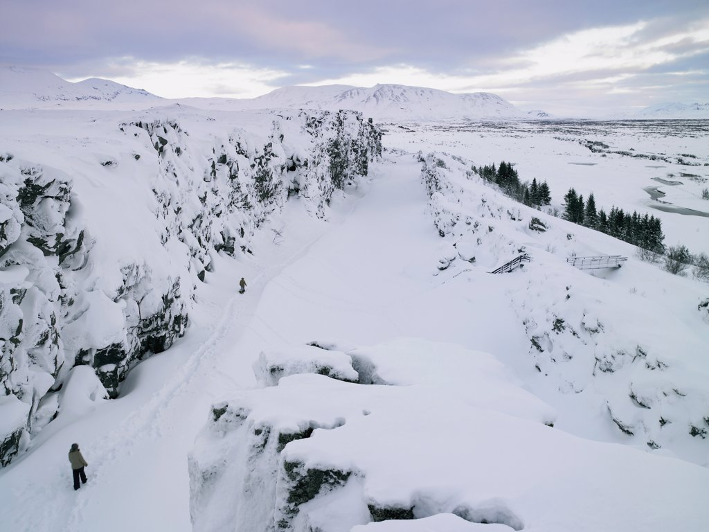 High angle view of two people walking in a snow covered landscape, Thingvellir National Park, Iceland : Stock Photo