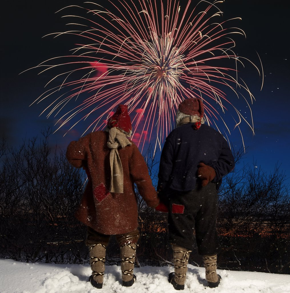 Iceland, New Year's Eve, Two Yule lads watching fireworks : Stock Photo