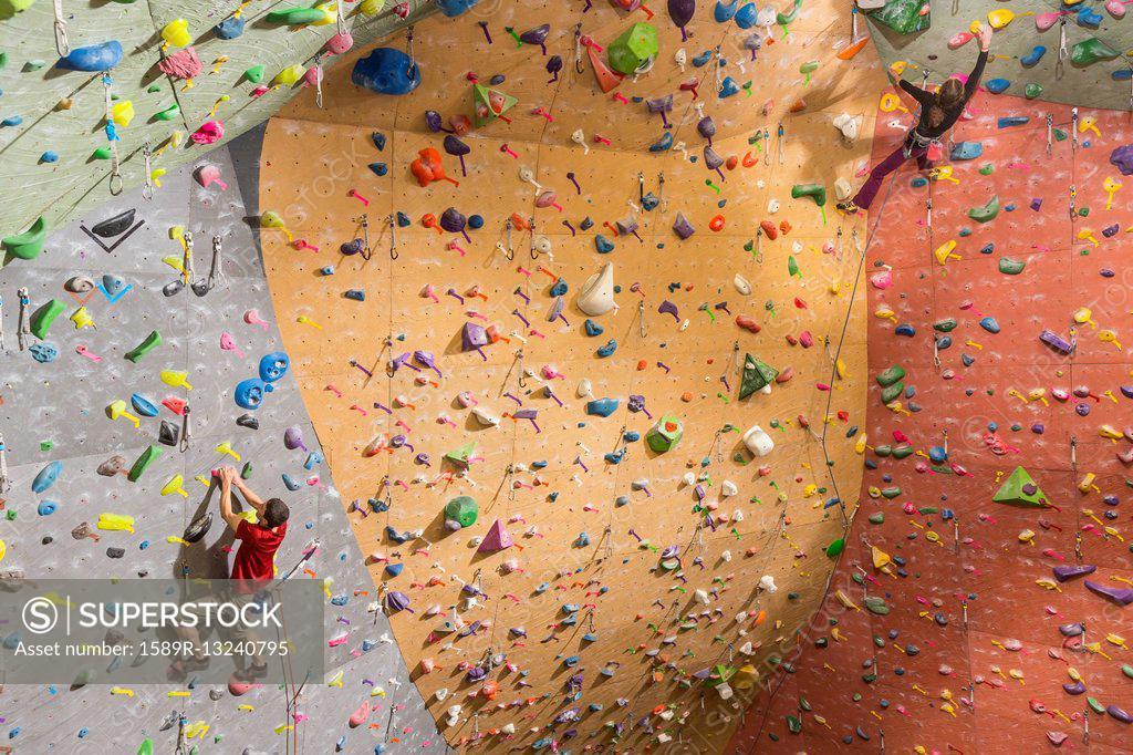 Stock Photo: 1589R-13240795 Caucasian climbers scaling rock wall