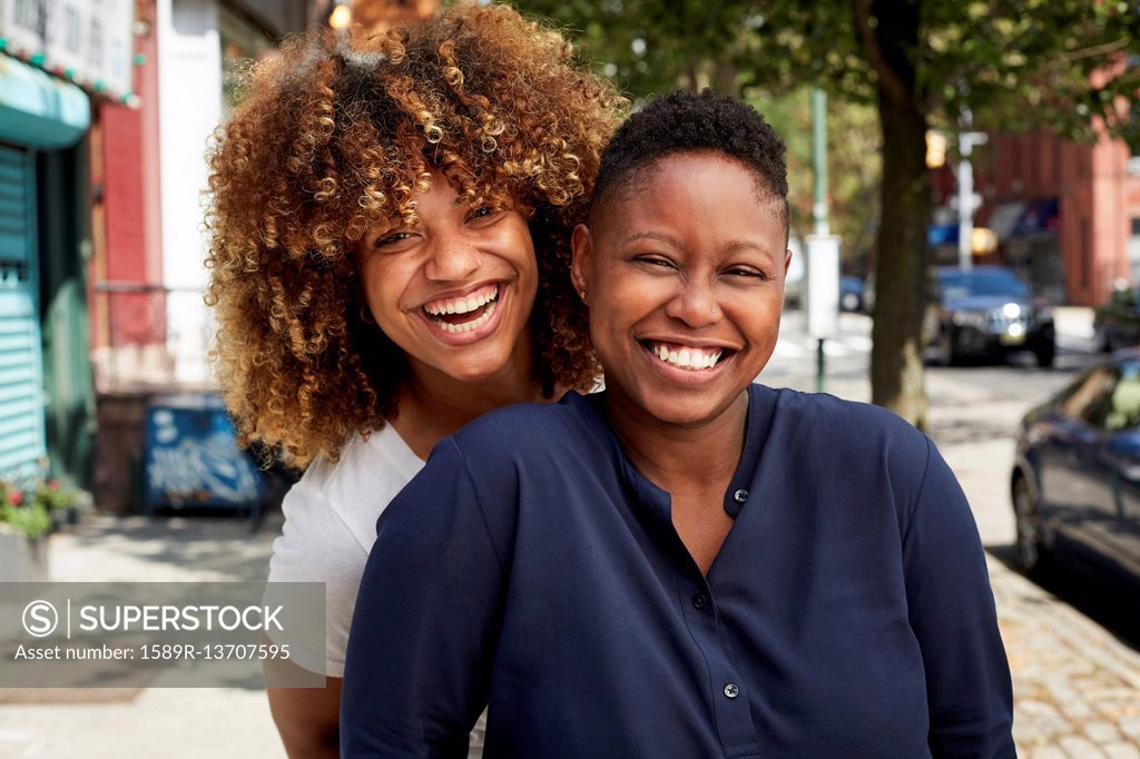 Stock Photo: 1589R-13707595 Black women smiling on city sidewalk