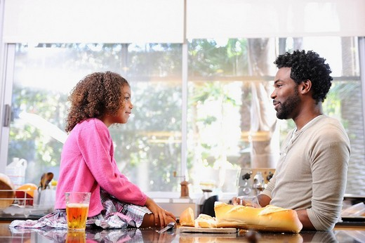 Father and daughter eating in kitchen : Stock Photo