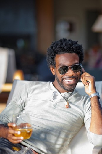 Black man talking on cell phone and drinking : Stock Photo