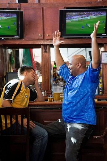 Cheering men watching television in sports bar : Stock Photo