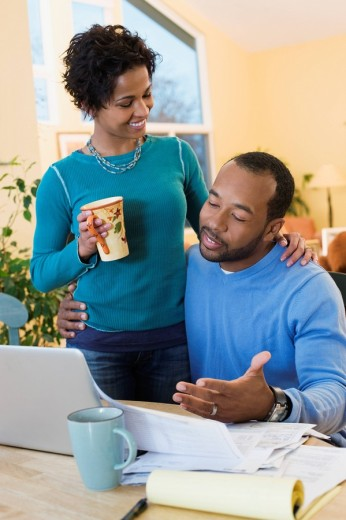 African American husband paying bills as wife watches : Stock Photo